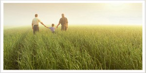 parents holding young child's hand and walking in field